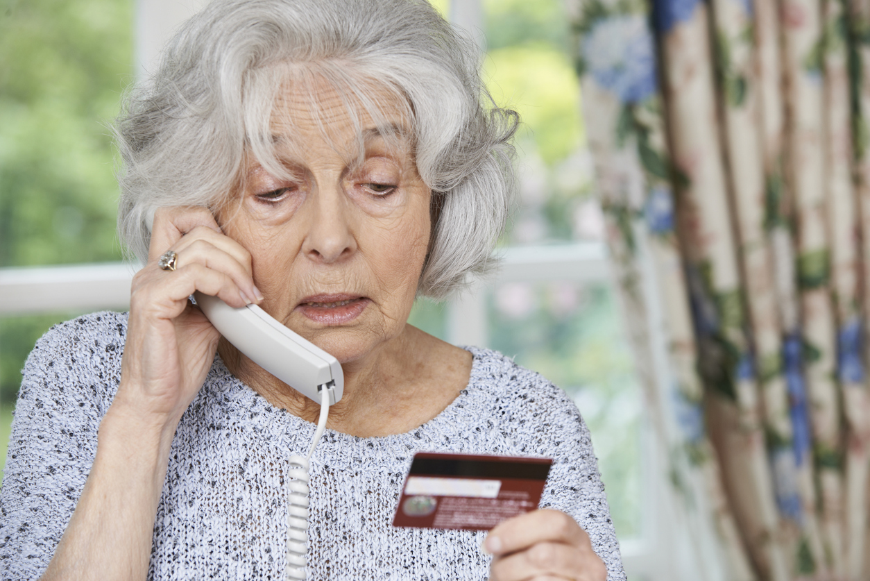 Senior Woman Giving Credit Card Details On The Phone Tax Scam