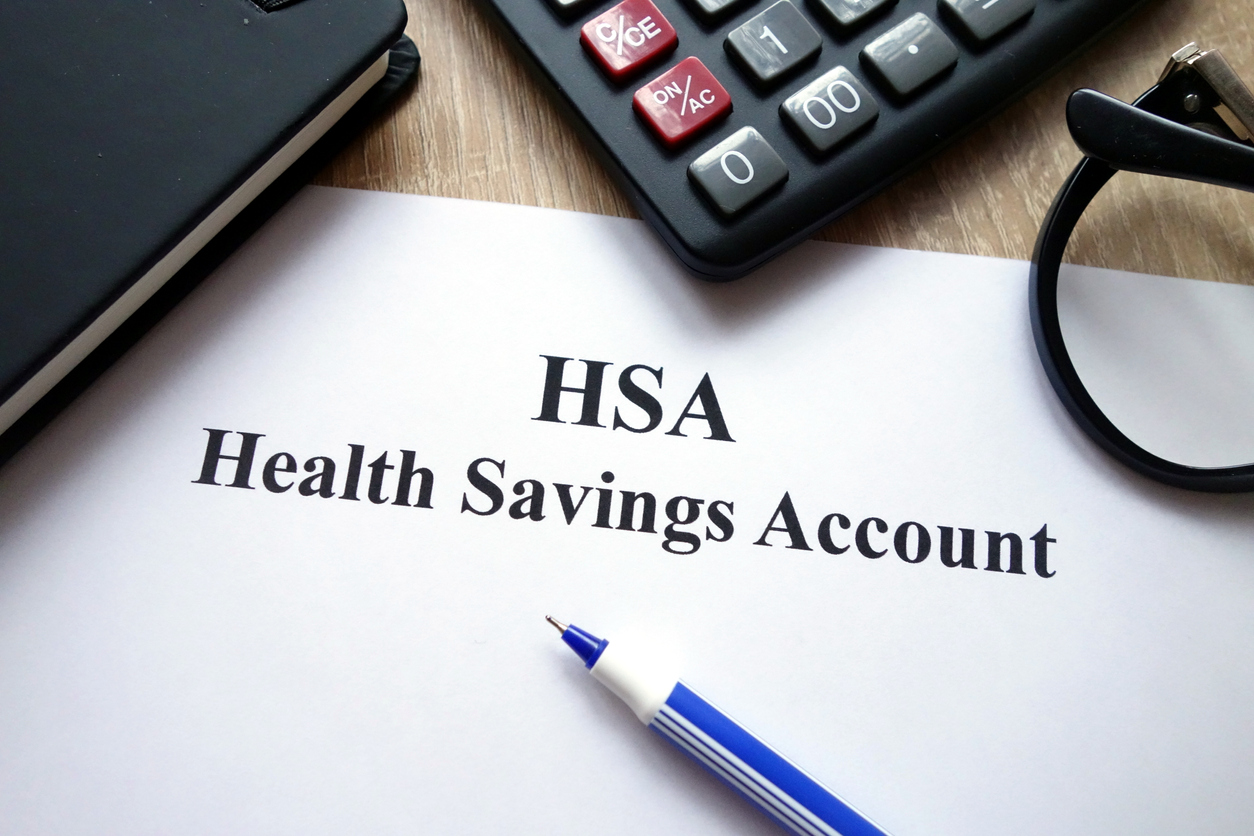 HSA health savings account document, calculator, pen and glasses on desk