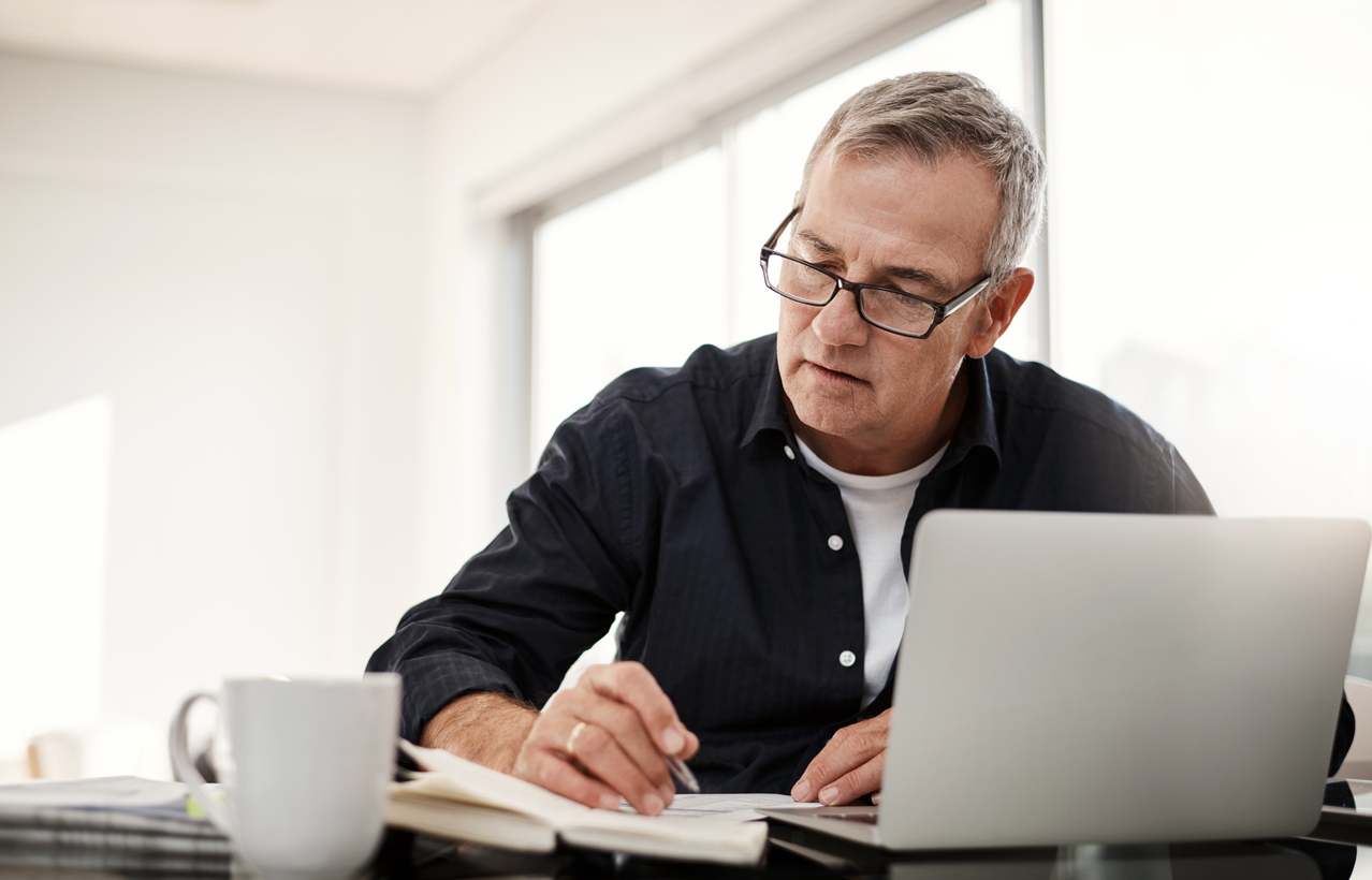 Shot of a mature man going through some retirement paperwork at home