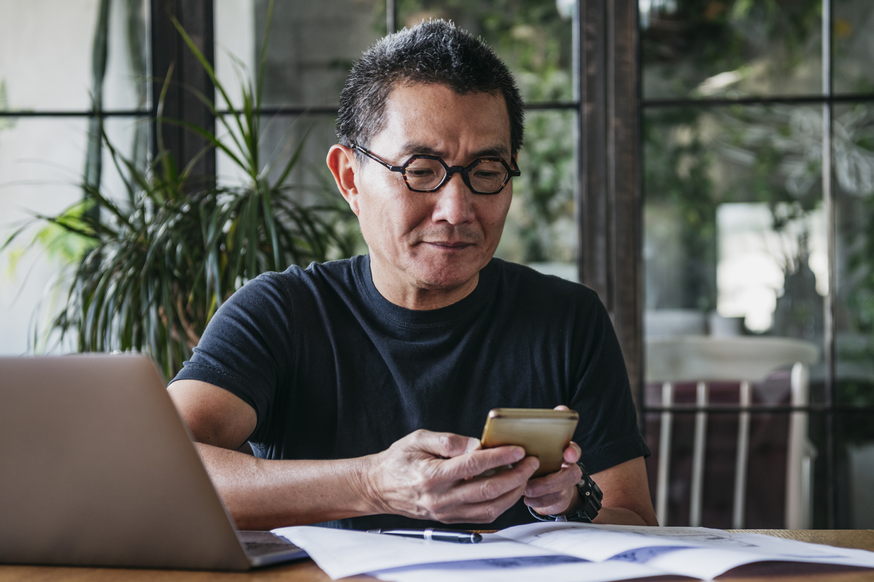 Man working remotely using mobile phone to make business payments.